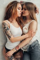 Tattooed sexy girls embracing shot against wall