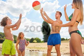 Familie mit zwei Kindern beim Ball spielen