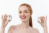 portrait of beautiful woman smiling while taking some facial cream isolated on white background with copy space.