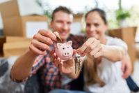 Glückliches Paar mit Sparschwein und Schlüssel