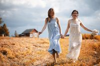 Two girls in dresses in autumn field