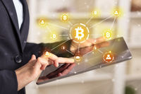 Business woman using tablet with bitcoin link network and online concept