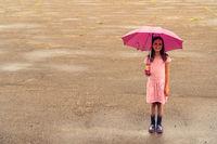 Girl with umbrella standing on wet asphalt