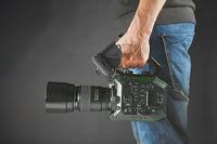 Kiev, Ukraine - April 22, 2018: cameraman holding his professional camcorder Panasonic AU-EVA1 in studio