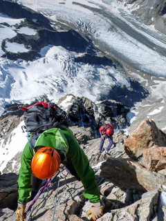 mountain climbers rappelling from a high mountain peak in the Swiss Alps