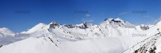 Panorama of mountains with snowy off-piste slope and blue sunlit sky at winter