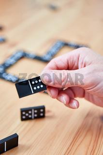 Hand hält einen Domino Spielstein