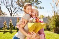 Tochter schenkt ihr Mutter einen Strauß Blumen