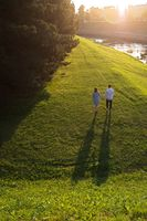 Young couple is walking along the river bank at sunset.
