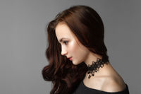 Pretty woman with long brown hairs on gray background.