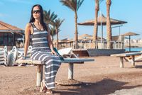 beautiful girl in a striped long dress and sunny goggles sits on a wooden bench against the background of an exotic sandy beach with palm trees, sun beds and sunny protective umbrellas