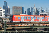 a red regional train of the rhine-main traffic in front of the skyline, frankfurt am main, germany