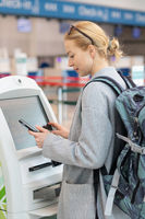 Casual caucasian woman using smart phone application and check-in machine at the airport getting the boarding pass.