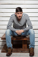 Beautiful man sits on a wooden table