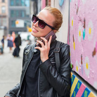 Woman talking on smartphone leaning against colorful graffiti wall in New York city, USA.