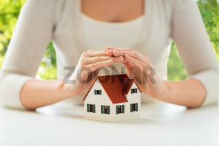 close up of woman protecting house model by hands