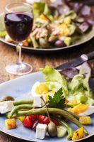 vegetarischer Salade Nicoise auf dunklem Holz