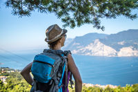 Hiking in Italy: Girl with straw hat is enjoying the view, summertime and beautiful landscape