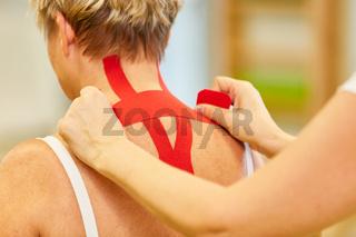 Frau bekommt ein rotes Kinesio Tape in den Nacken