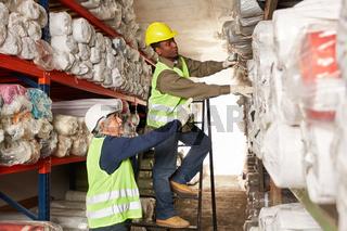 Arbeiter arbeiten zusammen im Teppichlager