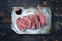 Japanese barbecue wagyu aged fillet steak slices as top view on a plate with copy space