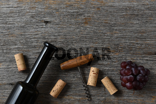 Wine bottle corks, corkscrew and grapes on a rustic old wood table, with copy space at the top