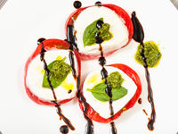 stacks of caprese salad with pesto on plate