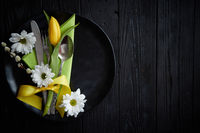 Easter spring table dishware composition with yellow tulip flower