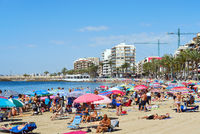 Torrevieja, Spain - June 10, 2019: Lot of people sunbath on popular Playa del cura sandy beach of Torrevieja city, high rise houses palm trees sunny idyllic day, concept of vacations relaxation. Spain