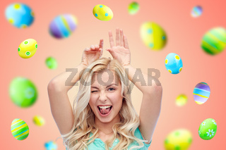 happy smiling young woman making easter bunny ears