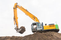 Excavator makes noise barrier with sandy soil