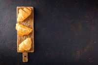 Freshly baked croissants on wooden cutting board, top view