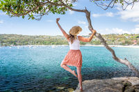 Happy woman dance pirouette beside tree by the ocean