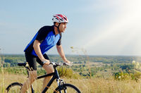 Male cyclist driving by rural dirt road outdoors