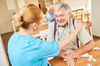 Altenpflegerin tröstet einen alten Mann