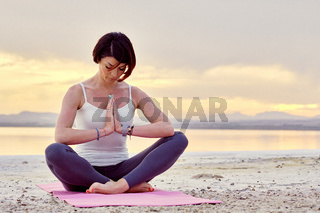 Alone yogi woman seated in lotus position meditating outdoors