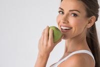 Woman biting green apple