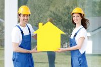 Two workers hold house model