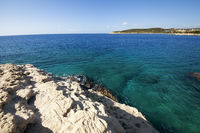 Blue clear sea and rocky sunlit coast at sunny summer morning