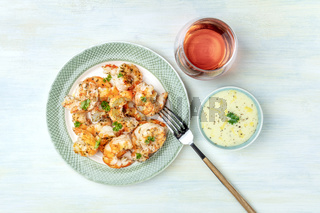 Fried shrimps with a glass of rose wine and a dip, shot from above on a light blue background