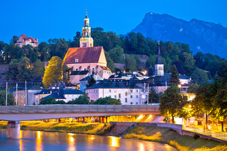 Salzburg historic architecture and mountain peaks background evening view