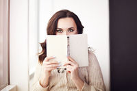 Young beautiful brunette woman  wearing knitted sweater reading book relaxing by the window