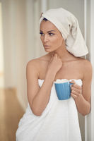 Pretty middle-aged woman wrapped in white towels