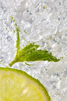 Fresh mint leaf and a slice of lime with bubbles in a glass with ice. Macro photo of refreshing drink