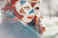 carnival, redhead woman with Venetian style mask with red feathers and gold pieces.