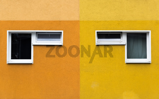 A pair of two windows on a yellow and orange facade