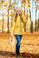 girl with apples in wicker basket at autumn park