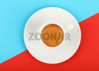 Full white espresso coffee cup on red and blue