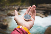 A beautiful male hand with a yellow watch strap holds a magnetic compass in a coniferous autumn forest against a mountain river with rocky stones. The concept of finding yourself the way and the truth