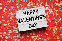valentines day lightbox sign on red paper background with confetti